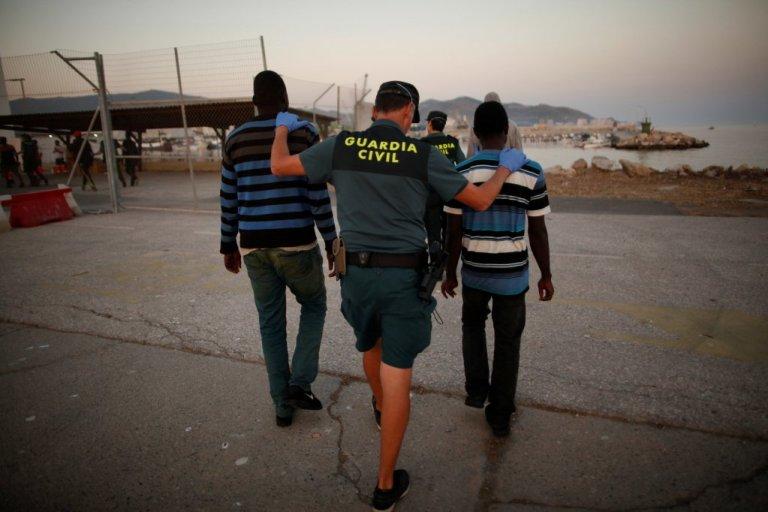 شرطي إسباني يقتاد مهاجرين/ أرشيف/ ANSA