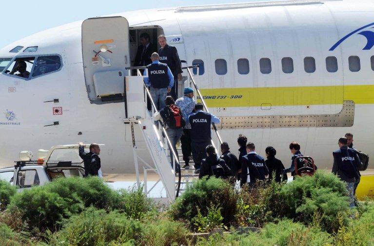 ansa / ضباط من الشرطة الإيطالية يصطحبون مهاجرين إلى الطائرة. المصدر: إي بي إيه/ كارلو فيرارو