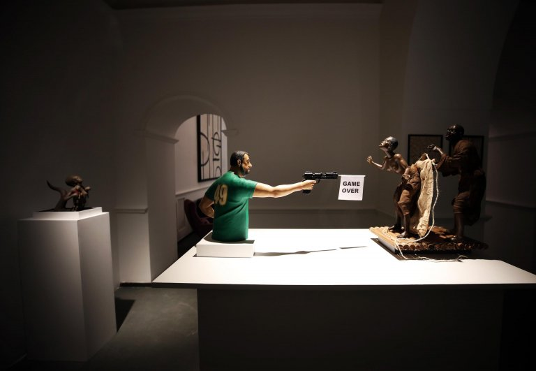 """The statue by artist Salvatore Scuotto which shows the former Italian interior minister Matteo Salvini shooting at two African migrant """"zombies""""   PHOTO:ANSA/US VIRGIN /Em Partena"""