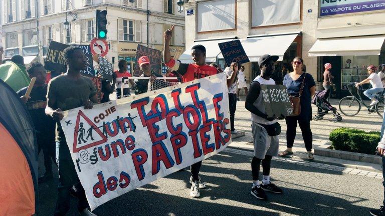 Karim (au centre, bras levé) a été désigné porte-parole des jeunes pour s'adresser à la préfecture. Crédit : Julia Dumont