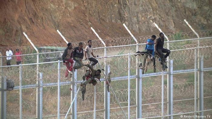 African migrants climb a fence into Ceuta