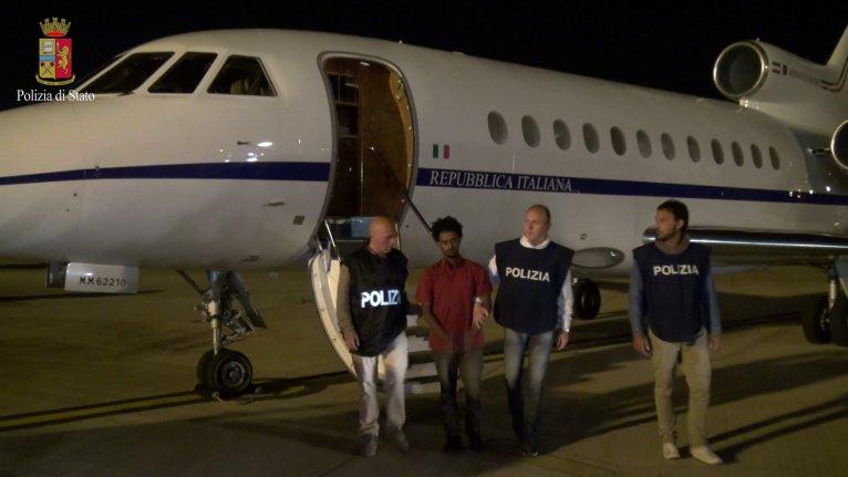 Italian Police Department/Handout via REUTERS |Les policiers italiens sont accompagnés d'un homme identifié par eux comme un trafiquant, mais qui ne serait qu'un migrant, Palerme, 8 juin 2016.