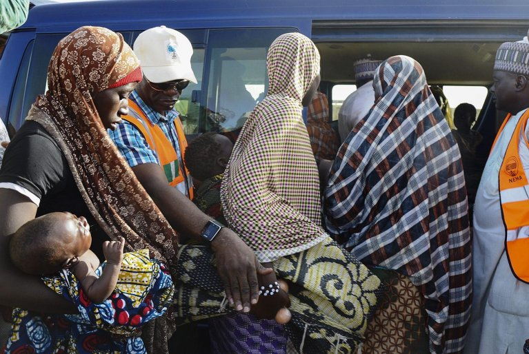 Nigerian refugees returning from the Republic of Niger are helped into a vehicle to be transported back home by personel from the National Emergency Management Agency (NEMA) | Photo: EPA/STR