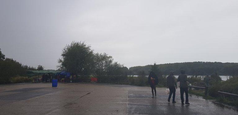 De jeunes migrants marchent sous la pluie sur l'un des parkings du bois du Puythouck à Grande-Synthe, dans le nord de la France, le 9 octobre 2019. Crédit : Anne-Diandra Louarn / InfoMigrants