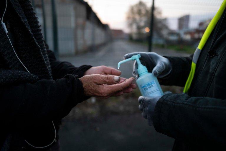 © AFP |Un bénévole du Secours catholique verse du gel hydroalcoolique lors d'une distribution de petits-déjeuners à Toulouse, le 3 avril 2020.