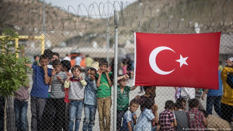 Refugee children in Gaziantep behind a fence with a Turkish flag on it | Photo: Picture-alliance/dpa/Moku/U.O.Simsek