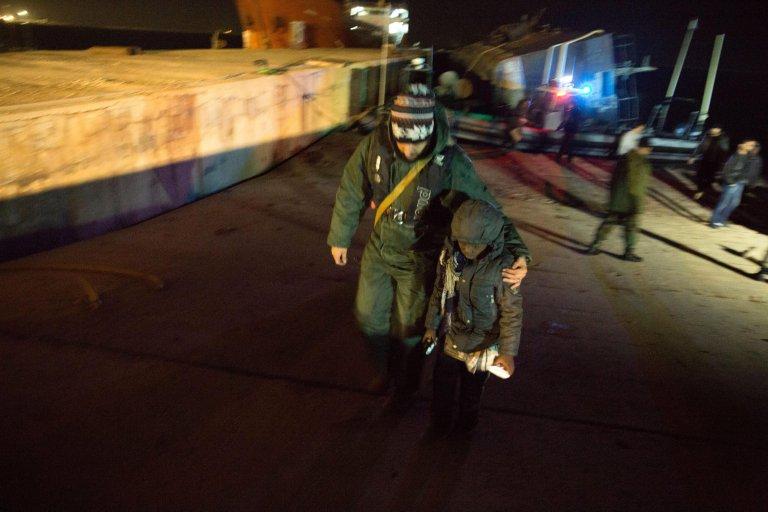 A Libyan coast guard officer escorting a boy at the port of Tripoli, Libya | Photo: EPA/STR