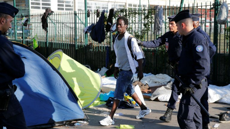 Un migrant et des policiers devant le centre de La Chapelle, à Paris, le 7 juillet 2017. Crédit : Reuters