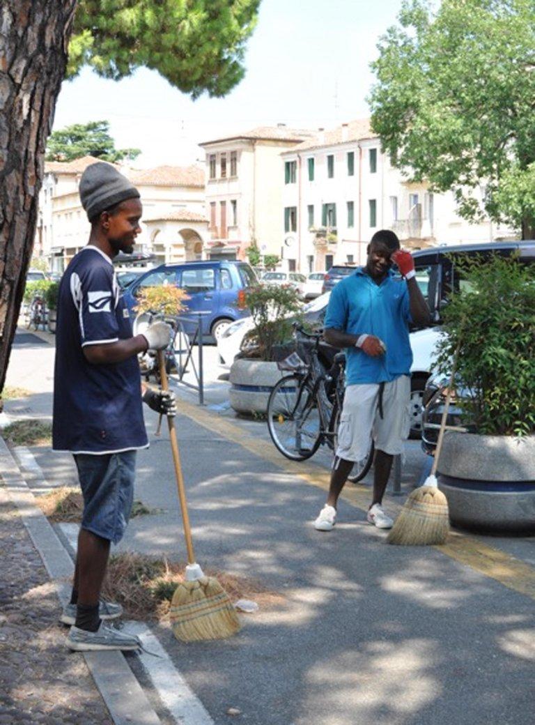 ansa / شابان نيجيريان فرايداي وسليستيان، ينظفان طواعية شوارع مدينة بادوا في إيطاليا. المصدر: كاميلا جالفان