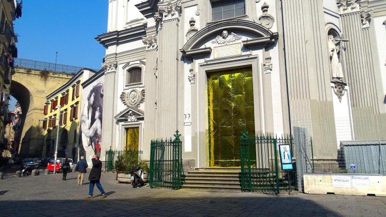 The thermal blankets issued to migrants decorate the gate of the Basilica di Santa Maria della Sanita in Naples | Photo: Project Eldorato