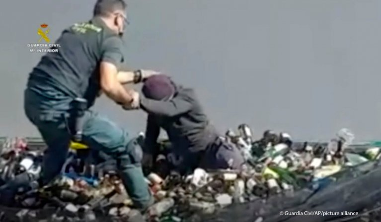 From video made available by the Guardia Civil: An officer helps a man out from under glass bottles in a container in Melilla, Spain, Friday February 19, 2021 | Photo: Picture-alliance/Guardia Civil via AP