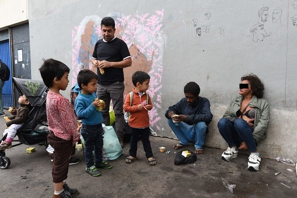 أطفال مهاجرون يراقبون مدمنة على المخدرات في حالة  نوبة عصبية أمام مركز لتقديم المساعدات في بورت دولا شابيل، باريس. 14 آب/ أغسطس 2018   مصدر: مهاجر نيوز