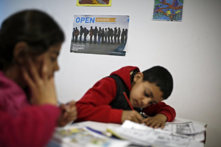Syrian children write as they take part in an English langauge lesson at the hospitality center on the island of Tilos, in southeastern Greece. Credit: EPA/ Yannis Kolesidis