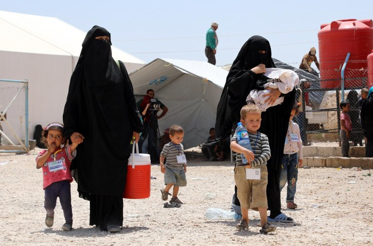 Wives of Islamic state fighters (IS) walk with their children upon their deportation from the al-Hol camp for refugees in al-Hasakah governorate in northeastern Syria on June 3, 2019. EPA/AHMED MARDNLI