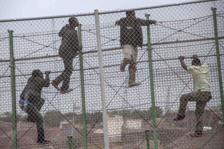 أرشيف / مهاجرون يحاولون عبور السياج الحديدي الفاصل بين جيب سبتة والحدود المغربية