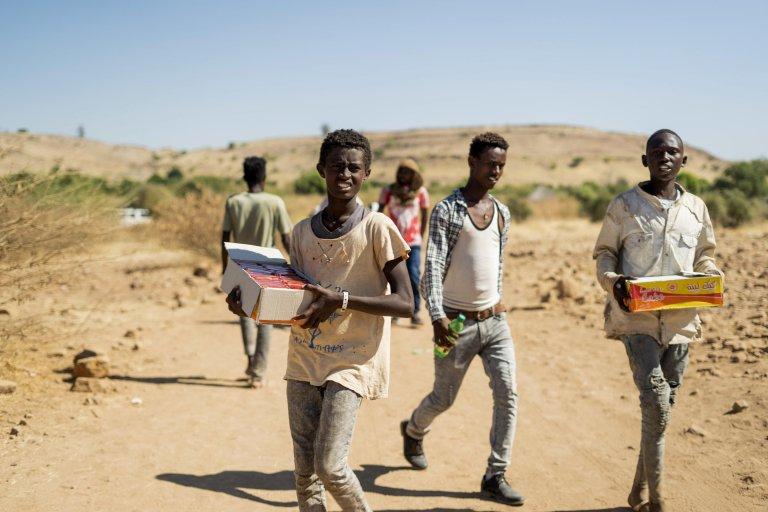لاجئون من إقليم تيغراي الإثيوبي يتلقون المساعدات في مخيم أم راكوبة بالسودان. المصدر: إي بي إيه/ علاء خير.