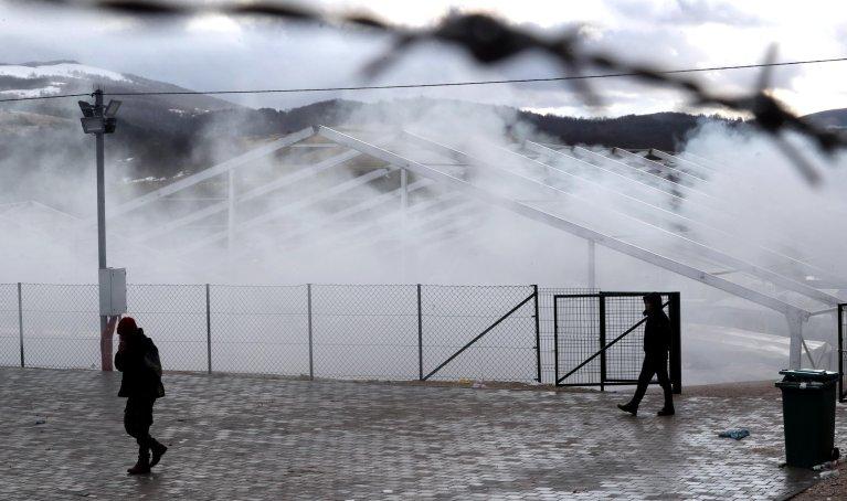 From file: Migrants walk in the smoke during a winter day in Lipa, near Bihac, in Bosnia and Herzegovina | Photo: EPA/FEHIM DEMIR