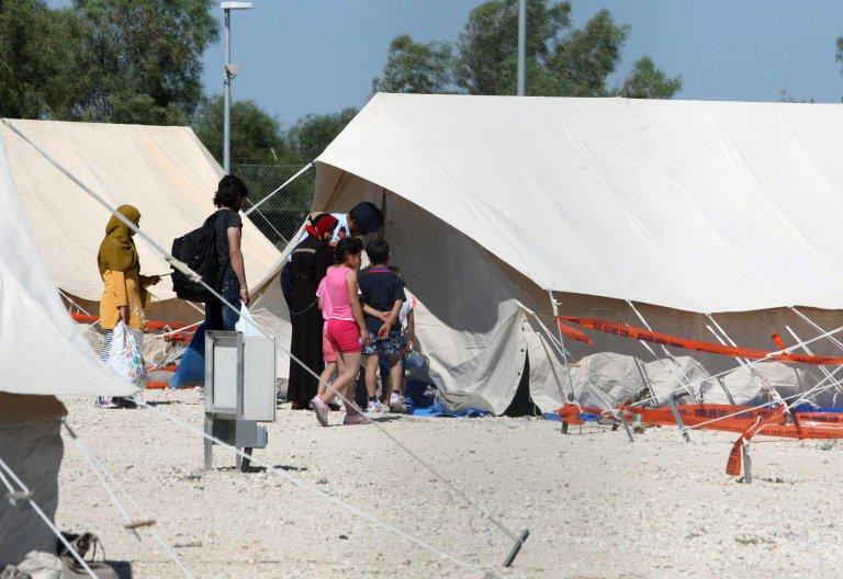 "Ansa / لاجئون يسيرون بجوار خيمة لدى وصولهم إلى إحدى مناطق الإقامة في قرية ""كوكينوترميثيا"" بالقرب من نيقوسيا. المصدر: ""إي بي إيه"" / كاتيا خريستودولوس."