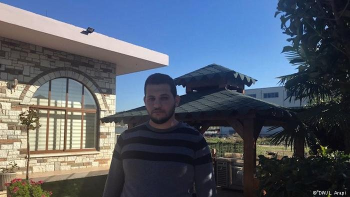 Young Mohamed Matwa in front of his family's restaurant business in Tirana