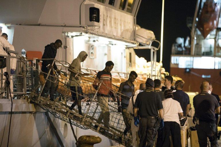 "Migrants disembark from Frontex ship ""Protector"" in the night at the port of Pozzallo, Sicily, Italy. Credit: ANSA/ Francesco Ruta"