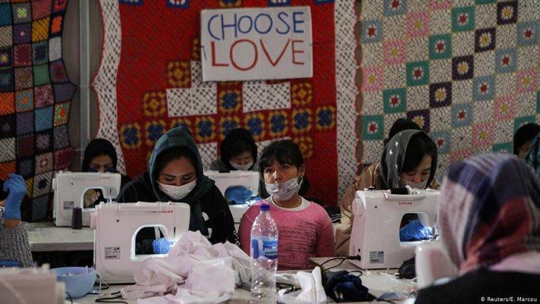 عکس تزئینی:  مهاجرانی که به صورت داوطلبانه برای سازمان «Team Humanity» کار می کنند، برای باشندگان کمپ موریا ماسک می دوزند./عکس: Reuters/E.Marcou