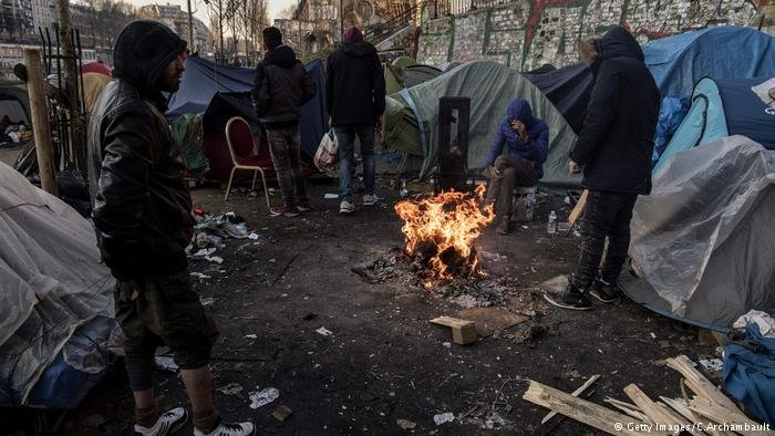 Migrants around a bonfire in Paris, February 2018