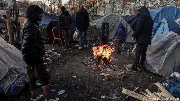 Migrants around a bonfire in Paris, February 2018