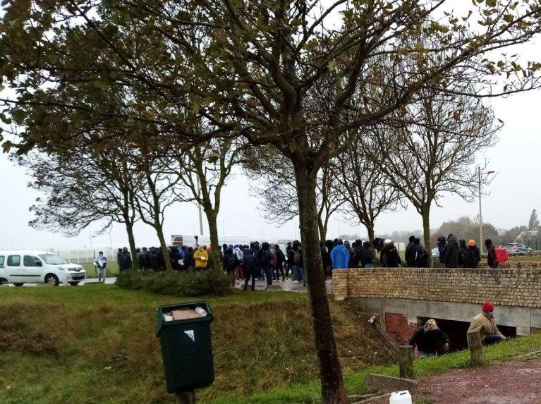 """مهاجرون أمام سيارات جمعية """"لافي أكتيف"""" في كاليه. الصورة: أوبيرج دي ميغران"""