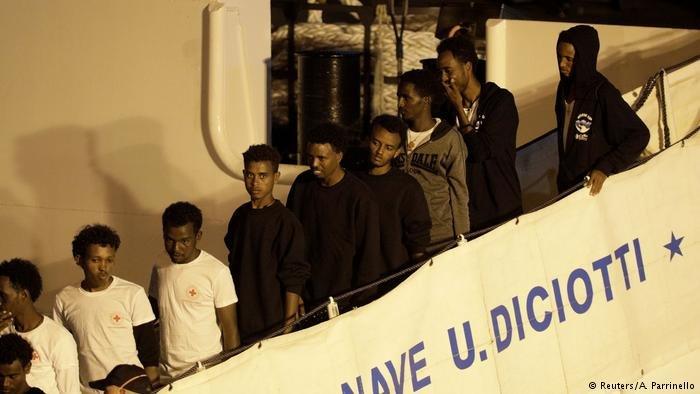 A stream of migrants disembark from the Diciotti, an Italian coast guard boat