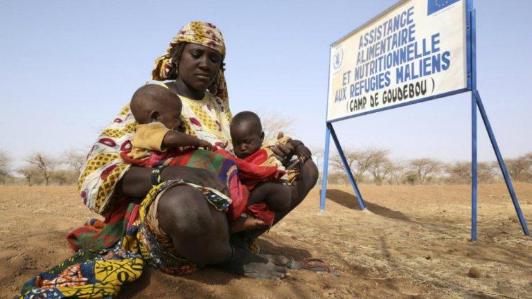 Une femme avec ses jumeaux à l'entrée du camp de réfugiés de Goudebou, au Burkina Faso.  Crédit : HCR / Brian Sokol