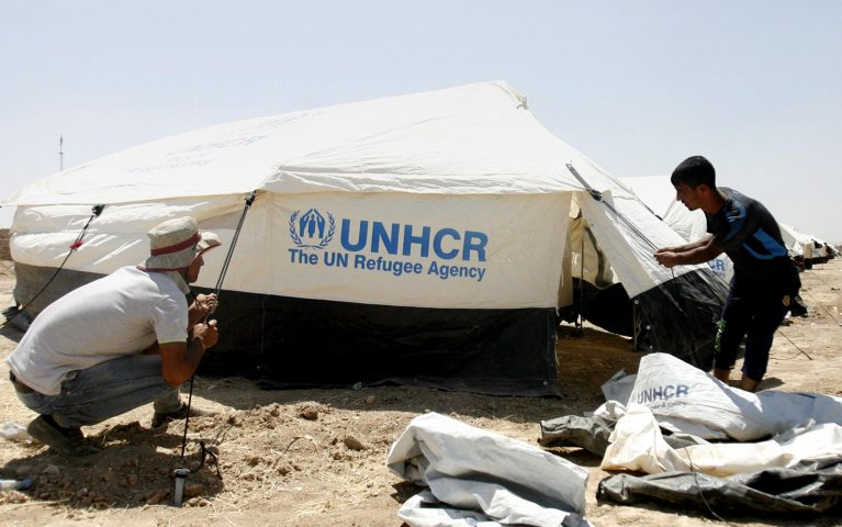 EPA photo showing UNHCR staff members while they erect tents at a camp for refugees forced to flee their homes in Erbil, Iraq