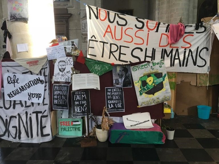 """""""نحن أيضاً بشر"""".. لافتات وضعها المهاجرون المضربون عن الطعام في كنيسة بيغويناج في بروكسل. المصدر: موسى أبوزعنونة/مهاجر نيوز"""