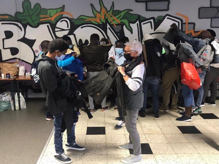 """متطوعة في جمعية """"دياكيتي"""" تساعد مهاجر في اختيار بعض الملابس، في مدينة بايون الفرنسية. المصدر: مهاجر نيوز"""