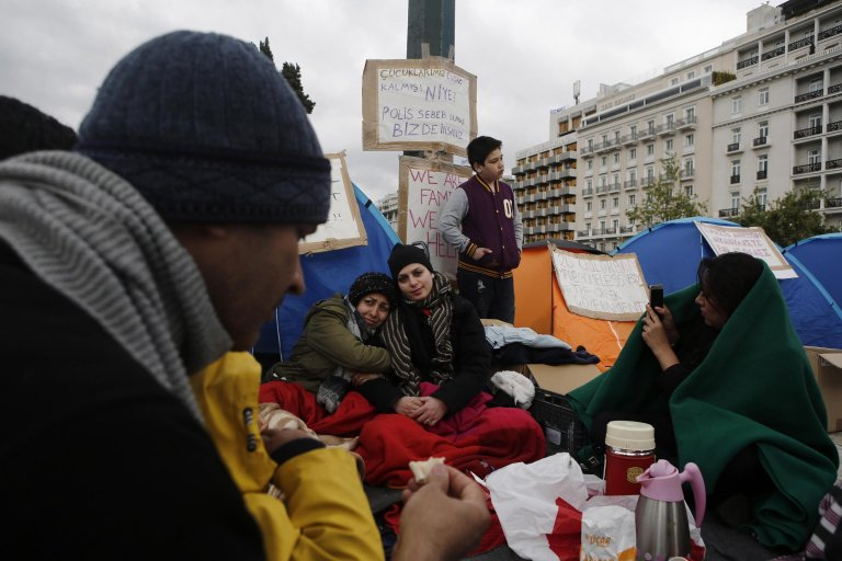 Refugees and migrants sit in front of tents as they protest outside parliament in central Athens, Greece. Photo: EPA/YANNIS KOLESIDIS