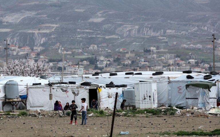 لاجئون سوريون أمام الخيام في مخيم الفيضة بالقرب من زحلة بوادي البقاع في لبنان. المصدر: إي بي إيه.