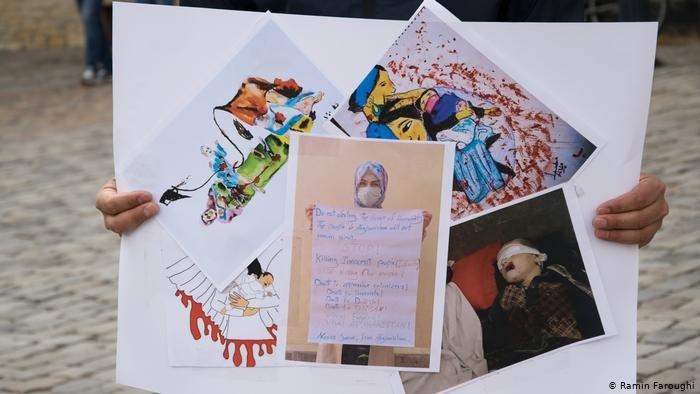 عکسی از مادران و کودکان قربانی در کابل در دست یکی دانشجویان معترض در شهر اوسنابروک آلمان