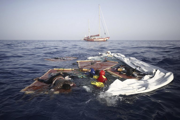 Rescue workers from the Proactiva Open Arms Spanish NGO retrieve the bodies of an adult and a child among the remains of a migrant boat. Credit: Proactiva Open Arms