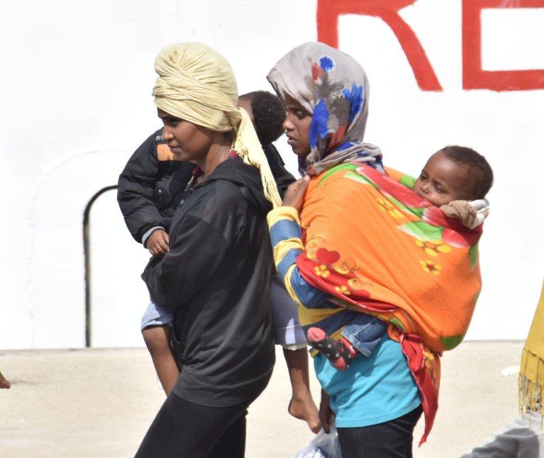 مهاجرون ينزلون من سفينة ديكيوتي التي حملت 932 مهاجرا وجثتين إلى كاتانيا. المصدر: ANSA.