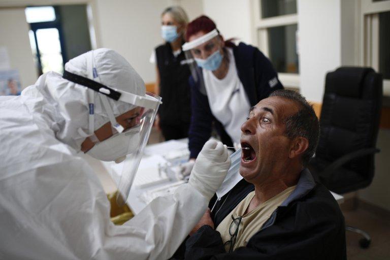A staff member of the Greek National Public Health Organiztion (EODY), Katerina Trikalioti (L), in protective gear, performs a COVID-19 test on Koufonissi island, Greece | Photo: EPA/Y. Kolesidis