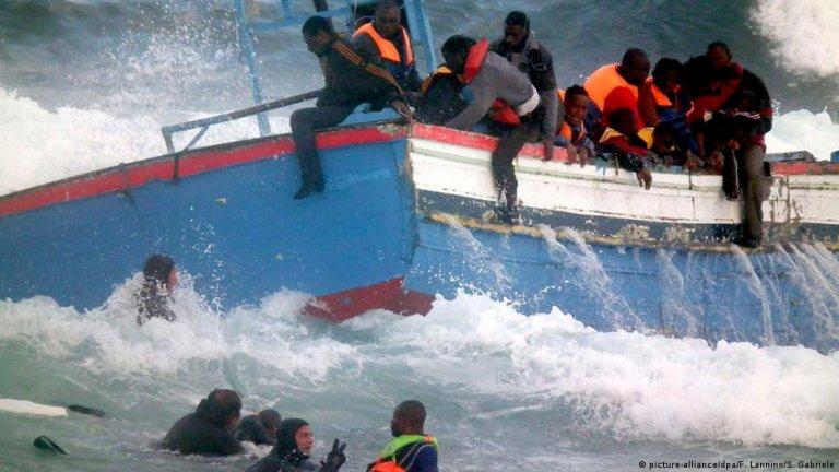 یک قایق پناهجویان که در آب ها در حال واژگون شدن است (عکس آرشیف)
