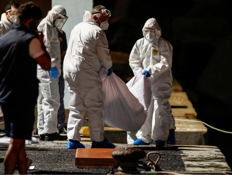 Des sauveteurs espagnols retirent quatre cadavres d'une embarcation de migrants, le 12 avril 2021. Crédit : Reuters