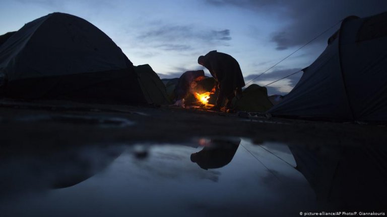 From file: Two migrants warm up over a makeshift fire after a rainfall, while waiting to be allowed to cross the border into North Macedonia at the northern Greek border station of Idomeni | Photo: Picture-alliance/AP Photo/P.Giannakouris