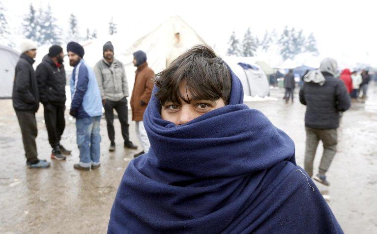 مهاجر يغطي نفسه خلال يوم ثلجي في مخيم فوشياك خارج مدينة بيهاتش في البوسنة والهرسك. المصدر: أنسا/ إي بي إيه/ فهيم دامير.