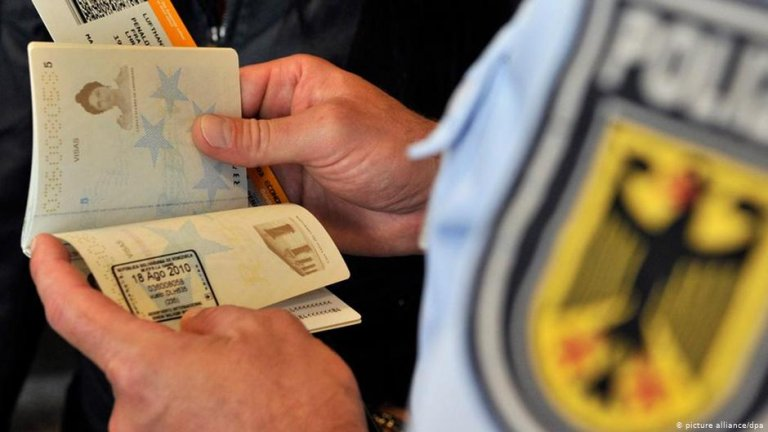 German police officer inspecting a passport visa | Photo: Picture-alliance/dpa