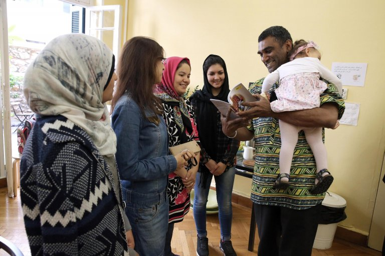 Amnesty International's Secretary General, Kumi Naidoo, holding in his arms the child of a migrant while talking with women migrants and refugees during his visit at the 'Melissa' network for migrant women in Athens.PHOTO/ARCHIVE/EPA/SIMELA PANTZARTZI