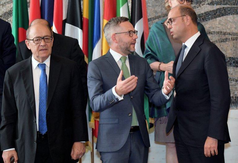 Le ministre français des Affaires étrangères Jean-Yves Le Drian (g), aux côtés de l'Allemand Michael Roth (c) qui discute avec le chef de la diplomatie italienne Angelino Alfano, lors de la réunion sur les migrants à Rome, le 6 juillet 2017. Crédit : AFP