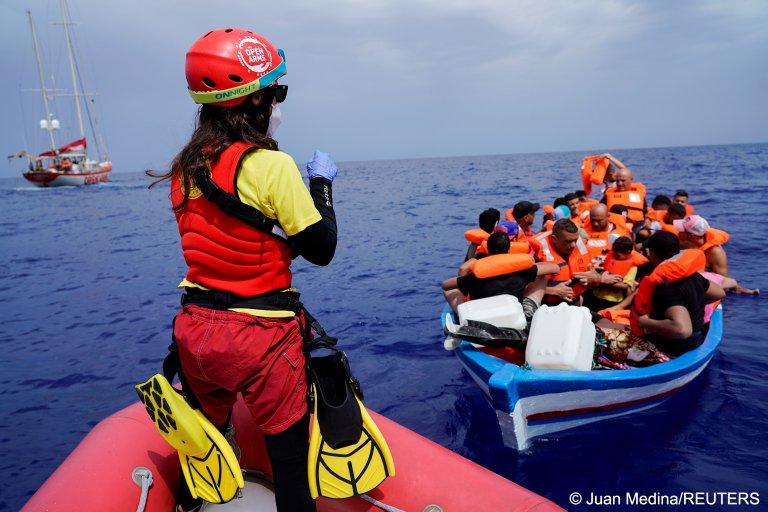 A member of NGO Proactiva Open Arms gives instructions to migrants on a wooden boat as they wait for the Italian coast guard near the island of Lampedusa on September 1, 2021   Photo: Juan Medina/REUTERS