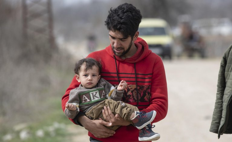 A migrant man and his son walk near the Greek border at the Pazarkule crossing in Edirne, Turkey, 9 March 2020. Many of the migrants who gathered at the border are from Syria   Photo: EPA/TOLGA BOZOGLU