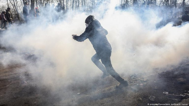 A migrant runs as Greek security forces intervene at the border between Turkey and Greece | Photo: Picture-alliance/AA/A.Hudaverdi Yaman