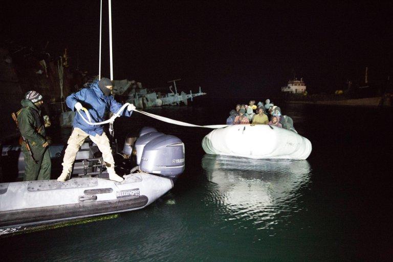 عناصر حرس السواحل الليبية تسحب حبلا لقارب مطاطي يقل مهاجرين في ميناء طرابلس. المصدر: إيه بي إيه.